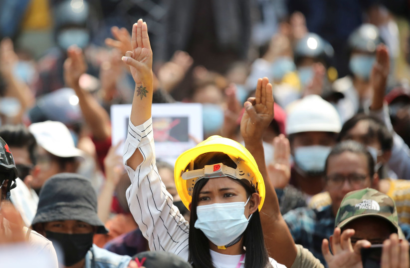 A woman shows a three-finger salute during a protest against the military coup in Naypyitaw (photo credit: REUTERS)