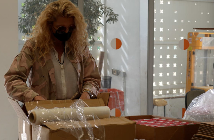 Former Israeli Supermodel Michaela Bercu helps pack boxes of food for the needy in the southern town of Yeruham. (photo credit: RAYMOND CRYSTAL/THE MEDIA LINE)