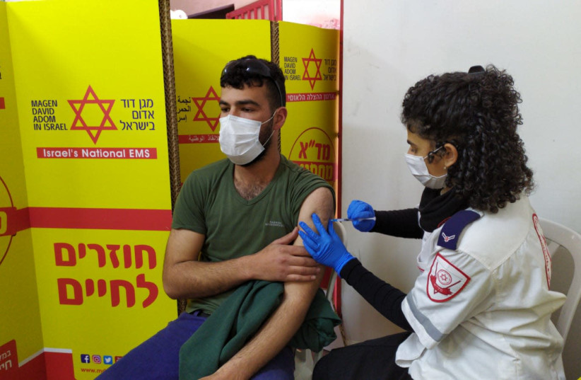 A Palestinian worker is given the coronavirus vaccine by Magen David Adom. (photo credit: MAGEN DAVID ADOM)