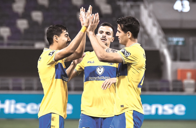 MACCABI TEL AVIV players celebrate during their 4-1 victory over Beitar Jerusalem, a result that lifted the yellow-and-blue into first place for the first time this season. (photo credit: ARIEL SHALOM)