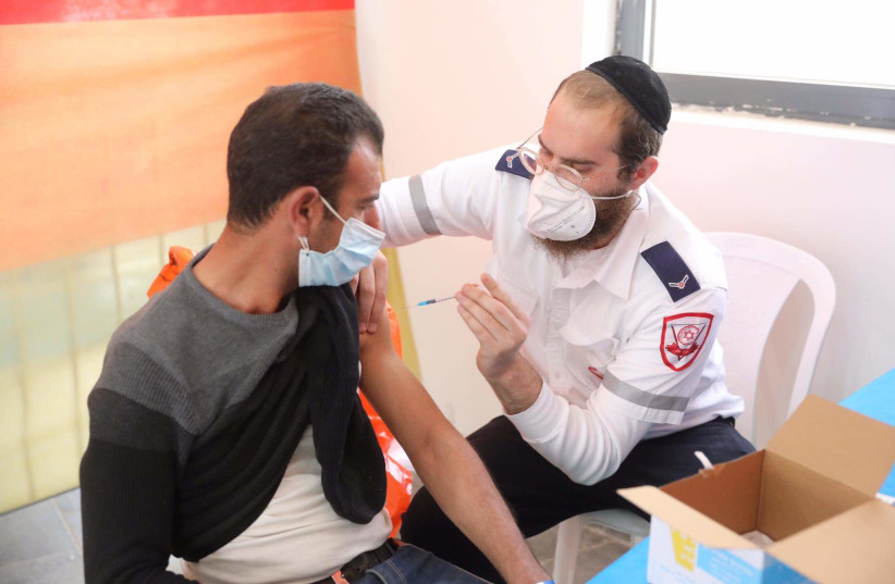 Palestinians receive the vaccine in a joint operation run by the Office of the Coordinator of the Government Activities in the Territories (COGAT), the Health Ministry and Magen David Adom that began on March 2nd 2021. (photo credit: MARC ISRAEL SELLEM)