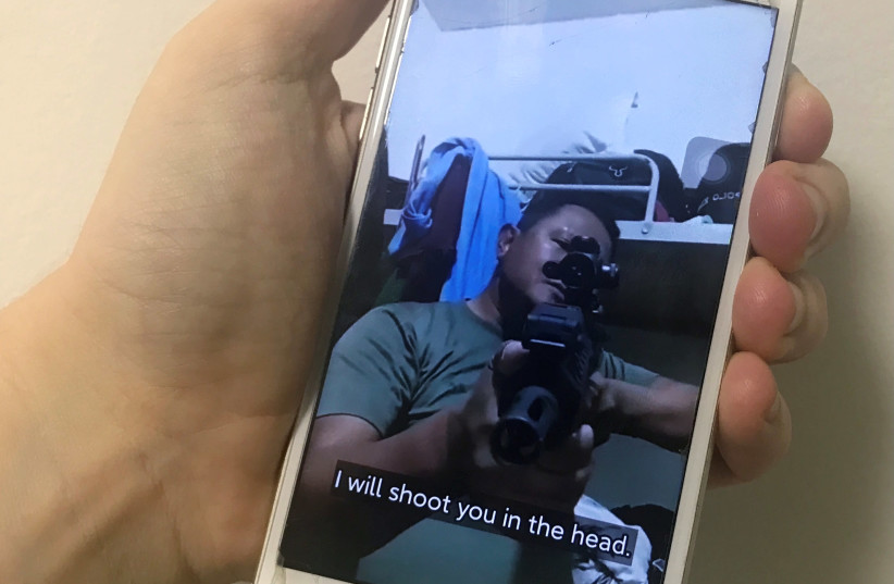 A mobile phone shows a picture of a Myanmar man in an army shirt threatening to shoot anti-coup protesters, in Singapore, March 4, 2021. (photo credit: REUTERS/FANNY POTKIN)