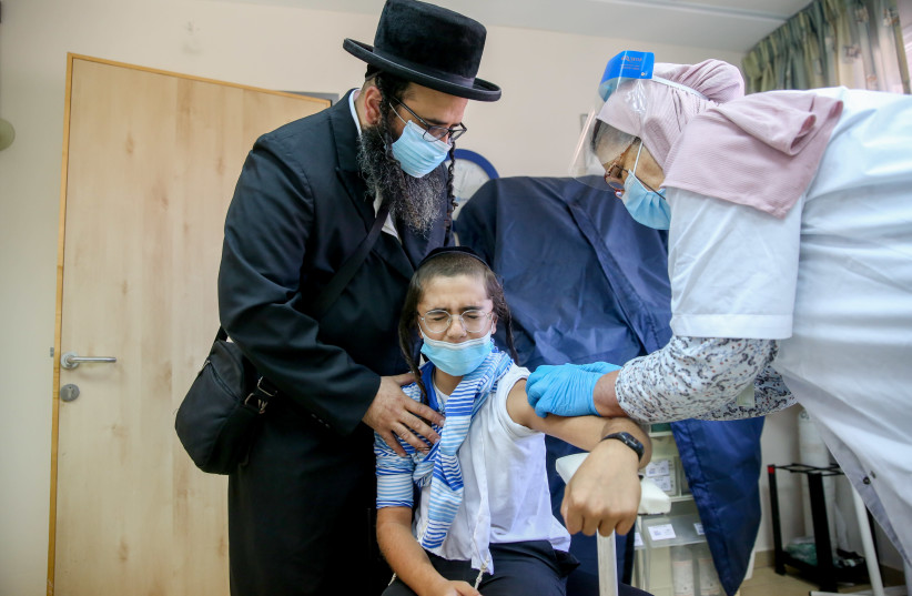 An ultra-Orthodox Jewish man and his child getting a flu vaccine at a health center in the northern Israeli city of Safed, October 22, 2020. (photo credit: DAVID COHEN/FLASH 90)