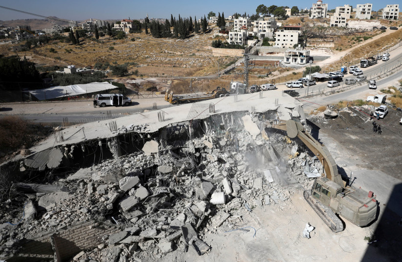 An IDF bulldozer demolishes a building near the security barrier in Waddi Hummus. July 22, 2019. (photo credit: AMMAR AWAD / REUTERS)