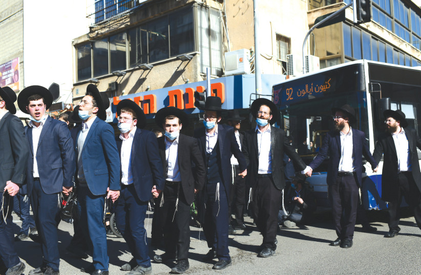 HAREDIM PROTEST police enforcement of lockdown orders related to the coronavirus in Bnei Brak in January. (photo credit: TOMER NEUBERG/FLASH90)