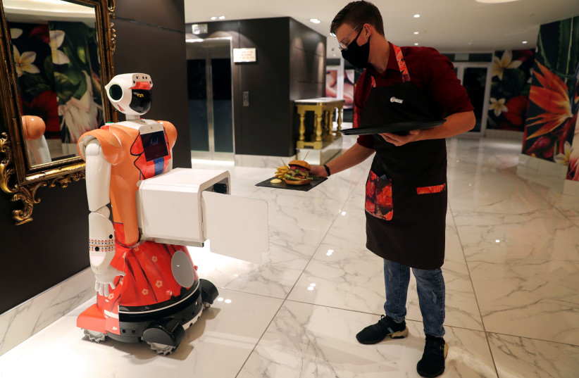 PLACING FOOD in a box attached to AI-powered robot Ariel for delivery to a guest at Johannesburg's Hotel Sky last month. The novel mirrors character development between an Artificial Friend and humans (photo credit: SUMAYA HISHAM/REUTERS)