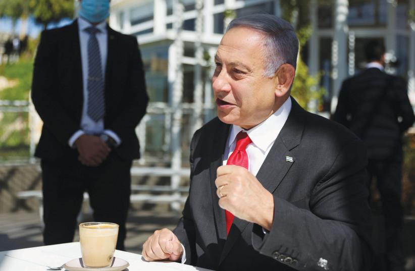 PRIME MINISTER Benjamin Netanyahu grabs a cup of coffee in Jerusalem this week. (photo credit: RONEN ZVULUN/REUTERS)