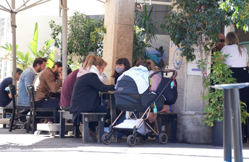 Patrons at a restaurant in Tel Aviv, Israel. March 7, 2021. (photo credit: RAYMOND CRYSTAL/THE MEDIA LINE)