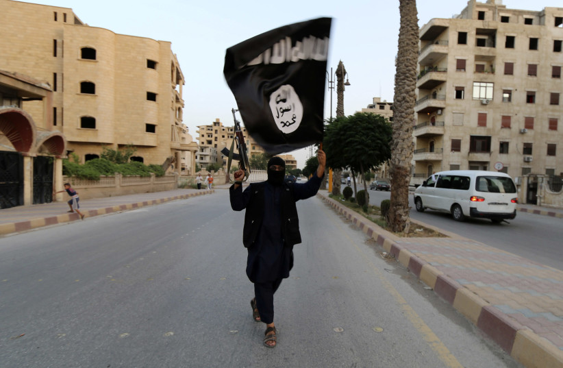 """A member loyal to the Islamic State in Iraq and the Levant (ISIL) waves an ISIL flag in Raqqa June 29, 2014. The offshoot of al Qaeda which has captured swathes of territory in Iraq and Syria has declared itself an Islamic """"Caliphate"""" and called on factions worldwide to pledge their allegiance, a st (photo credit: REUTERS/STRINGER)"""