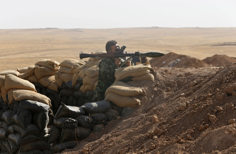 A Kurdish peshmerga fighter takes up position with a rocket-propelled grenade (RPG) launcher at the front line against the Islamic State, in Khazir September 7, 2014. Islamic State launched a lightning advance through northern and central Iraq in June, declaring an Islamic caliphate. With the help o (credit: REUTERS/AHMED JADALLAH)