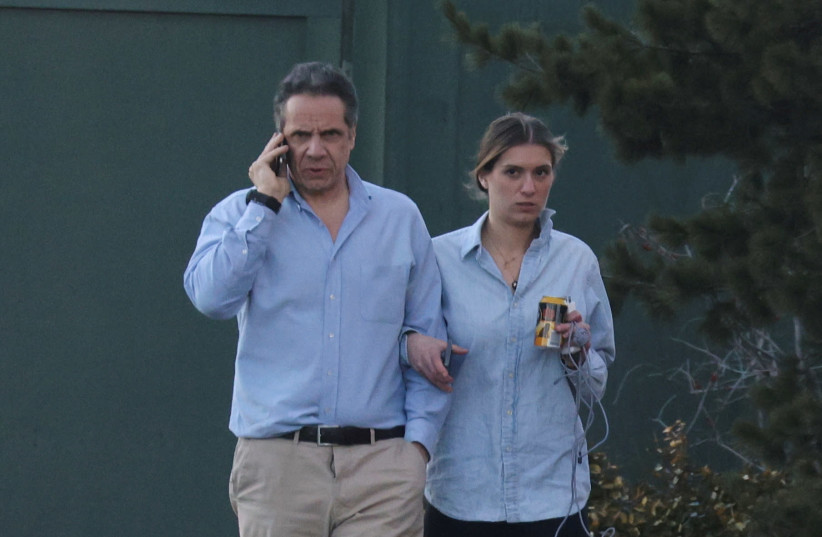 New York Governor, Andrew Cuomo, walks with his daughter on the grounds of the Governor's Mansion following allegations that he had sexually harassed young women, in Albany, New York, U.S., March 12, 2021. (photo credit: ANGUS MORDANT/ REUTERS)