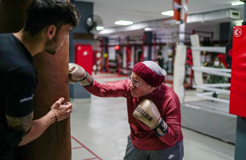 Nancy Van Der Stracten, 75-year-old suffering from Parkinson's disease, practices boxing with her trainer Muhammed Ali Kardas at a boxing club in the southern resort city of Antalya, Turkey, February 26, 2021.  (photo credit: UMIT BEKTAS / REUTERS)