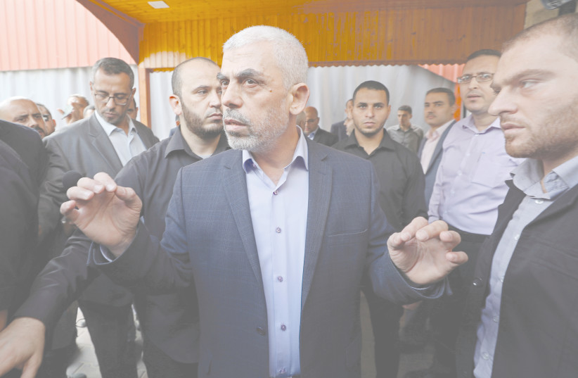 GAZA'S HAMAS CHIEF Yahya Sinwar talks to the media before meeting with Palestinian Central Election Committee Chairman Hana Naser, in Gaza City in 2019. (photo credit: MOHAMMED SALEM/ REUTERS)
