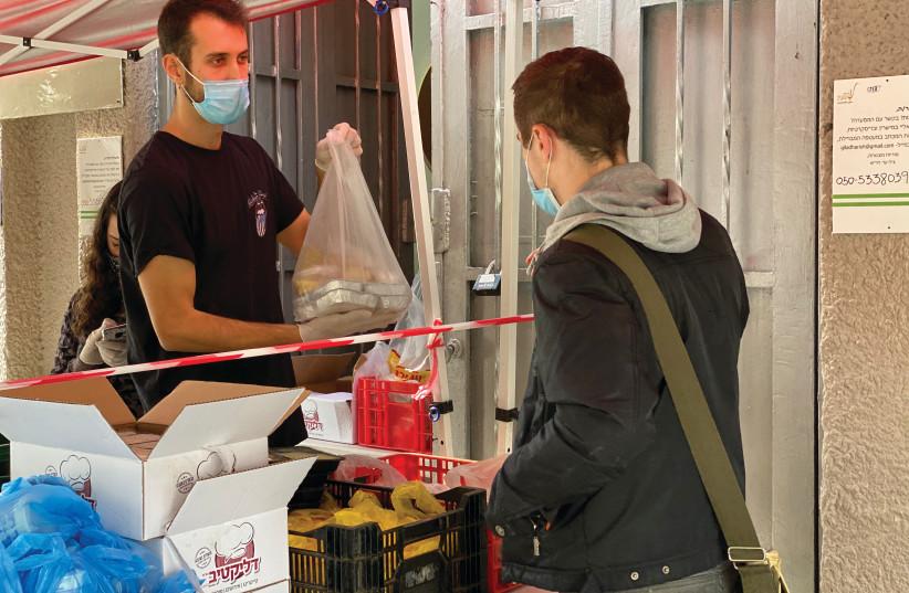 LEKET ISRAEL volunteers distribute food at a soup kitchen in Tel Aviv.  (photo credit: LEKET ISRAEL)
