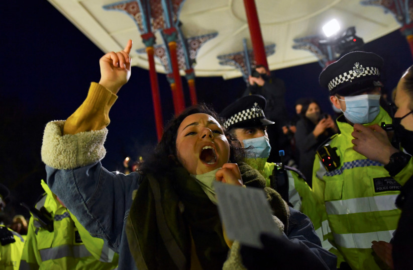 A woman shouts near police members as people gather at a memorial site at the Clapham Common Bandstand, following the kidnap and murder of Sarah Everard, in London, Britain, March 13, 2021. (photo credit: REUTERS)