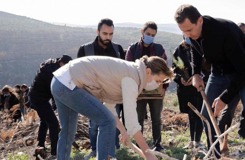 Syria's President Bashar Assad and his wife Asma, plant trees in city of Draykish, near Tartous, Syria December 30, 2020. (photo credit: SANA/HANDOUT VIA REUTERS)