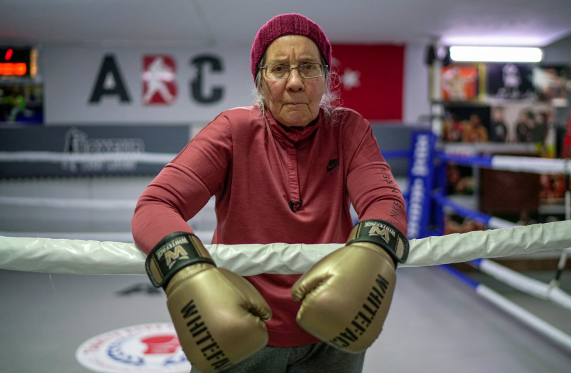 Nancy Van Der Stracten, 75-year-old suffering from Parkinson's disease, poses during a boxing practice break in the ring at a boxing club in the southern resort city of Antalya, Turkey, February 26, 2021. (photo credit: REUTERS/UMIT BEKTAS)