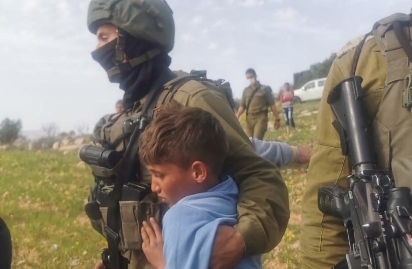 IDF soldiers detain Palestinian children near Havat Maon in the West Bank, March 10, 2021. (photo credit: NASSR NAWAJ'AH B'TSELEM)