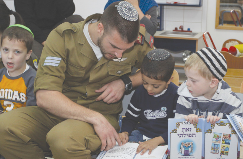 A SOLDIER in an IDF conversion course interacts with children praying at their kindergarten in 2013. (photo credit: GERSHON ELINSON/FLASH90)