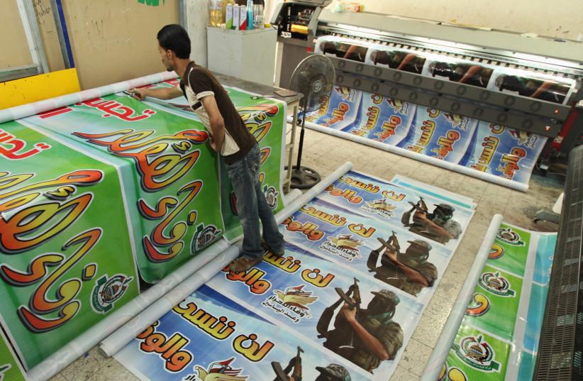 Un Palestinien imprime des affiches en préparation d'un échange de prisonniers entre le Hamas et Israël à Gaza, 2011 (crédit : MOHAMMED SALEM/ REUTERS)