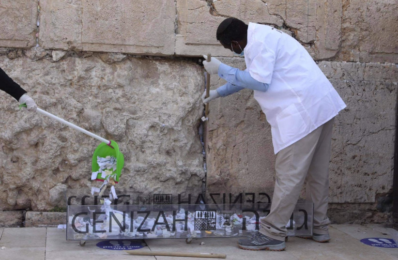 Notes in the Western Wall are cleared before Passover, 2021 (photo credit: MARC ISRAEL SELLEM)