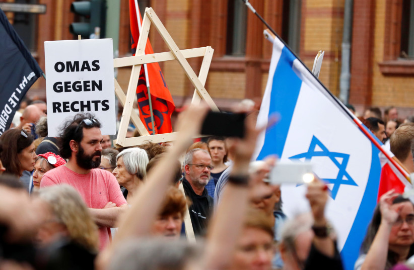 "A man carries a wooden Star of David as people attend a demonstration themed with the slogan ""#unteilbar"" (indivisible) to protest against antisemitism, racism and nationalism in Berlin, Germany, October 13, 2019. (photo credit: REUTERS/HANNIBAL HANSCHKE)"