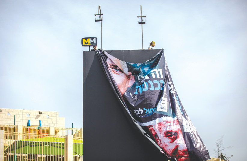 WORKERS HANG a large election campaign poster in Jerusalem last week. (photo credit: YONATAN SINDEL/FLASH90)