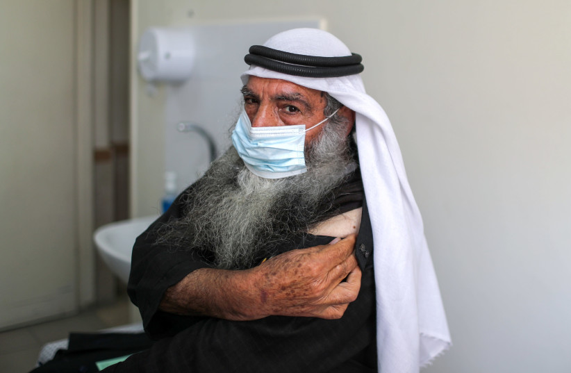 A Palestinian man waits to be vaccinated against the coronavirus disease (COVID-19), in Gaza City (photo credit: REUTERS)