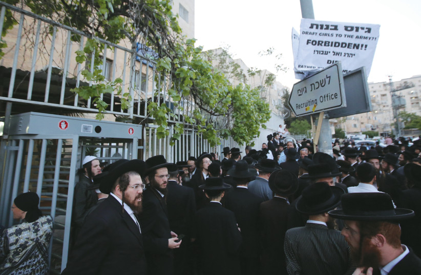 HUNDREDS OF haredi protesters gather outside the IDF recruitment office in Jerusalem's Mekor Baruch neighborhood to protest IDF induction, in 2018. (photo credit: MARC ISRAEL SELLEM/THE JERUSALEM POST)