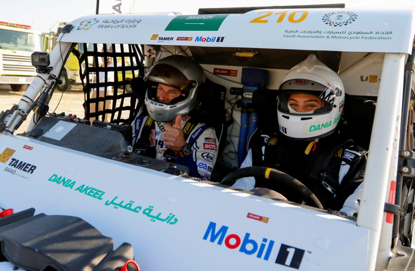 SAUDI FEMALE rally driver, Dania Akeel, and her co-driver, Laurent Lichtleuchter, sit in her T1-Buggy during the first stage of Sharqiyah International Baja Rally, in Dhahran, Saudi Arabia, earlier this month. (photo credit: HAMAD I MOHAMMED/REUTERS)