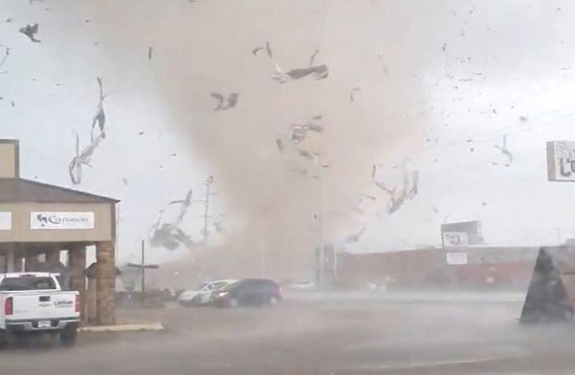 A screen grab from a social media video shows a tornado wrecking havoc in Jonesboro, Arkansas, U.S. March 28, 2020. (photo credit: REUTERS)