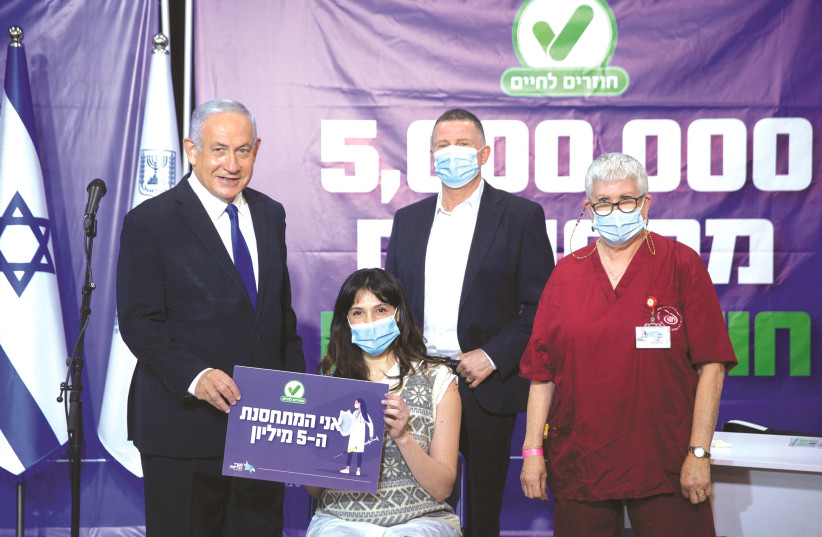 PRIME MINISTER Benjamin Netanyahu and Health Minister Yuli Edelstein are seen during a visit to a Leumit Health Care Services COVID-19 vaccination center in Tel Aviv, with the five millionth Israeli who received a vaccination, last week.  (photo credit: MIRIAM ALSTER/FLASH90)