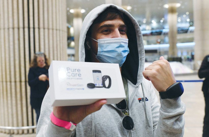 PASSENGERS ARRIVING from Frankfurt earlier this month receive electronic bracelets for their quarantine period.  (photo credit: TOMER NEUBERG/FLASH90)