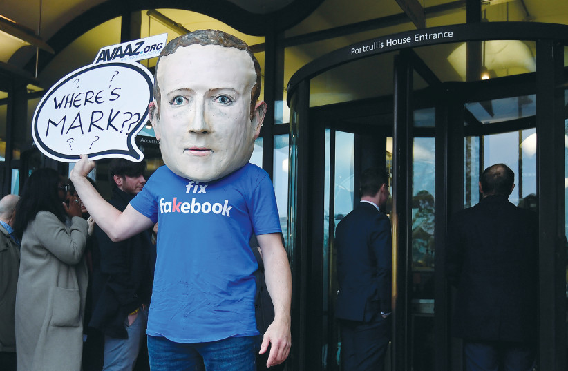 A campaigner from a political pressure group wears a mask of Facebook founder and CEO Mark Zuckerberg in London in November 2018.  (photo credit: TOBY MELVILLE/REUTERS)