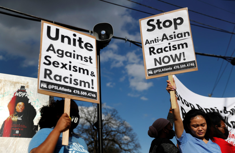 Demonstrators hold signs during a demonstration following the deadly shootings in Atlanta, Georgia, U.S. March 18, 2021.  (photo credit: SHANNON STAPLETON / REUTERS)