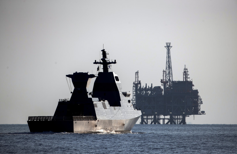 """The Saar-6 corvette, a warship dubbed """"Shield"""", cruises near the production platform of Leviathan natural gas field after a welcoming ceremony by the Israeli navy marking its arrival, in the Mediterranean Sea off the coast of Haifa on December 1, 2020.  (photo credit: RONEN ZVULUN / REUTERS)"""