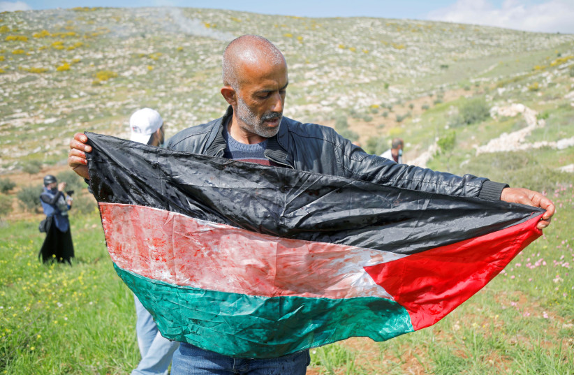 A man holds a Palestinian flag stained with blood of a mortally wounded Palestinian during a protest against Israeli settlements, in Beit Dajan in the Israeli-occupied West Bank March 19, 2021. (photo credit: REUTERS/RANEEN SAWAFTA)