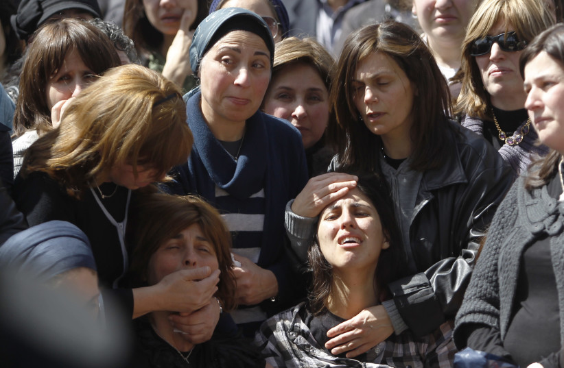 A relative of Miriam Monsonego mourns during funeral in Jerusalem (photo credit: REUTERS)