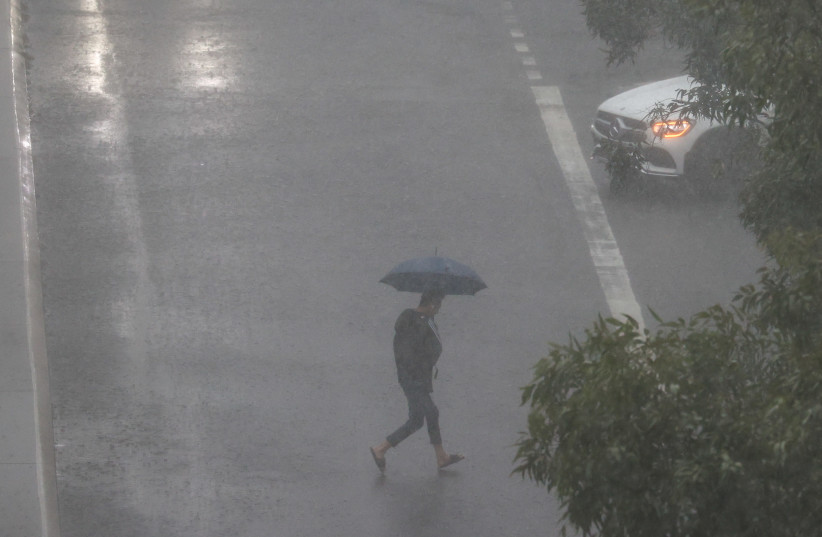 A person crosses a street in severe rain as the state of New South Wales experiences widespread flooding, in Sydney, Australia, March 20, 2021. (photo credit: LOREN ELLIOTT/REUTERS)