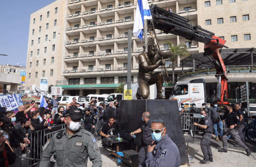 Artist chains himself to statue in protest at Paris Square, March 21, 2021 (photo credit: MARC ISRAEL SELLEM)