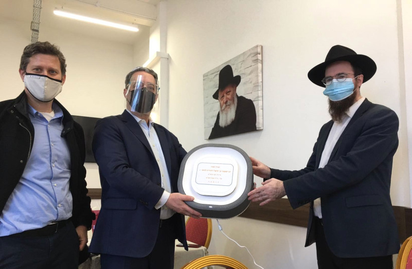 Installation of Covid-19 Air Purifiers at Golders Green Chabad House located in London, with the presence of Rabbi Shneor Glitzstein (R), Eyal Landau, and Sagi Barkai. (photo credit: AURA AIR)