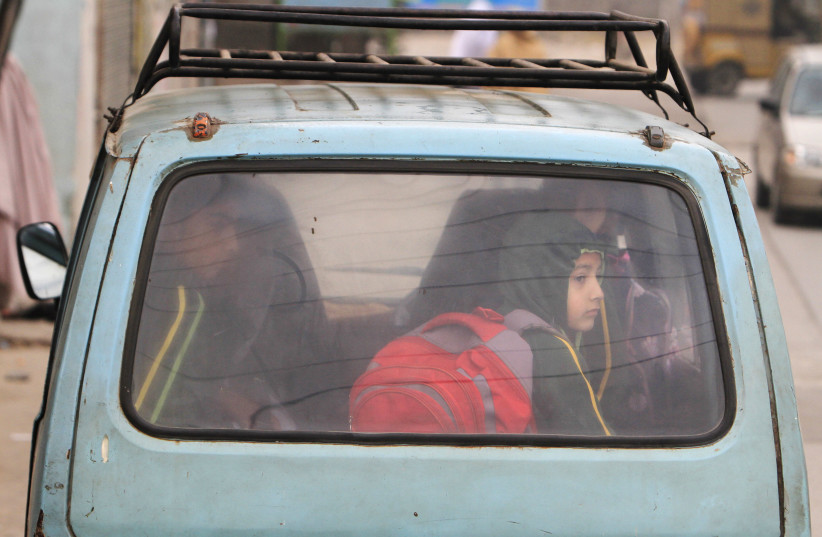 A boy sits in a van with others while heading to their school in Pakistan. (photo credit: FAISAL MAHMOOD/REUTERS)