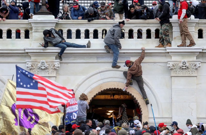 A mob of supporters of former US President Donald Trump fight with members of law enforcement at a door they broke open as they storm the US Capitol Building in Washington, US, January 6, 2021. (photo credit: REUTERS/LEAH MILLIS/FILE PHOTO)