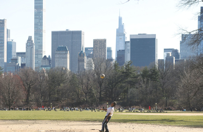 A MAN plays with a soccer ball in a field at Central Park on spring equinox, in the Manhattan borough of New York City, last week. (photo credit: CAITLIN OCHS/REUTERS)