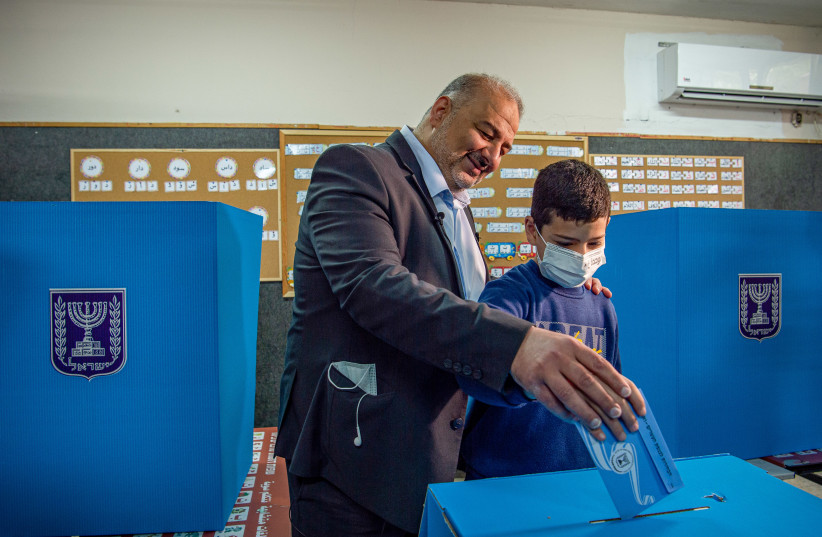 Ra'am Party leader Mansour Abbas casts his vote at a voting station in Maghar, during the Knesset Elections, on March 23, 2021. (photo credit: FLASH90)