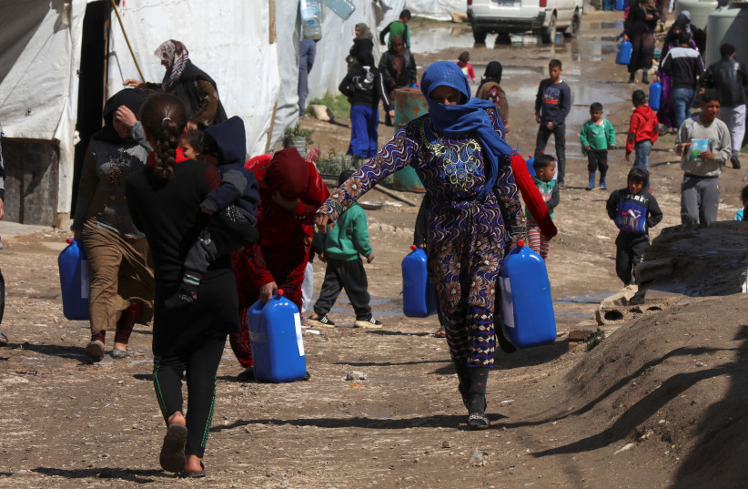 Syrian refugees walk as they carry containers at an informal tented settlement in the Bekaa valley, Lebanon March 12, 2021 (photo credit: MOHAMED AZAKIR/REUTERS)