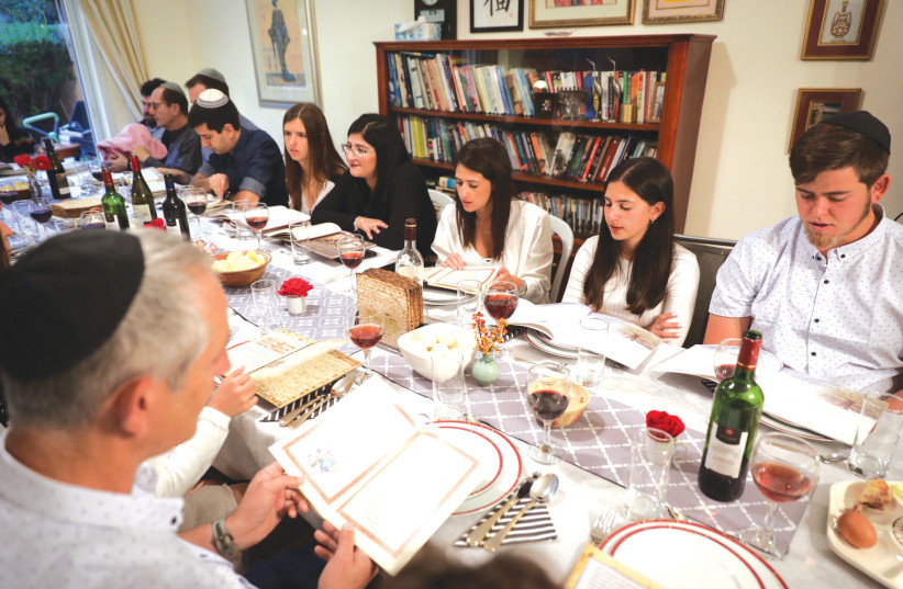A FAMILY gathers for their Seder on the first night of Passover, in Rishon Lezion, in 2018.  (photo credit: NATI SHOHAT/FLASH90)