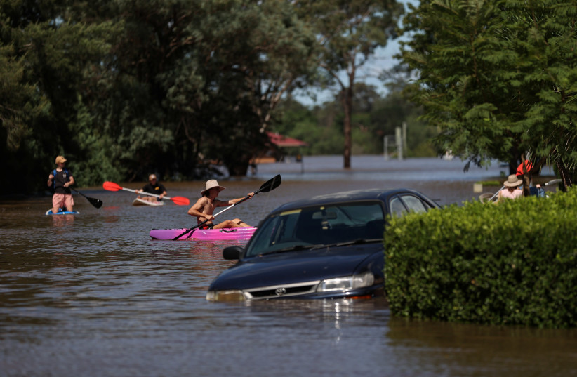People using kayaks and paddle boards navigate a residential neighbourhood inundated with floodwaters as severe flooding affects the suburb of McGraths Hill in Sydney, Australia, March 24, 2021. (photo credit: LOREN ELLIOTT/REUTERS)