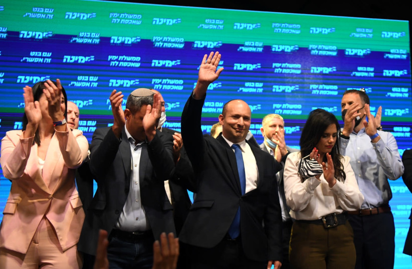 Naftali Bennett and party members are seen with Yamina supporters at the party headquarters in Petah Tikva, on elections night, on March 23, 2021. (photo credit: AVI DISHI/FLASH90)