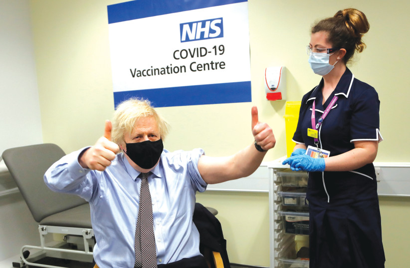 BRITISH PRIME MINISTER Boris Johnson receives a dose of the Oxford/AstraZeneca COVID-19 vaccine earlier this month. (photo credit: FRANK AUGSTEIN/REUTERS)
